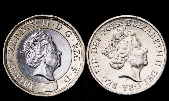 A old issue one pound coin (R) is pictured alongside a newly issued 12-sided one pound coin in London on March 28, 2017.