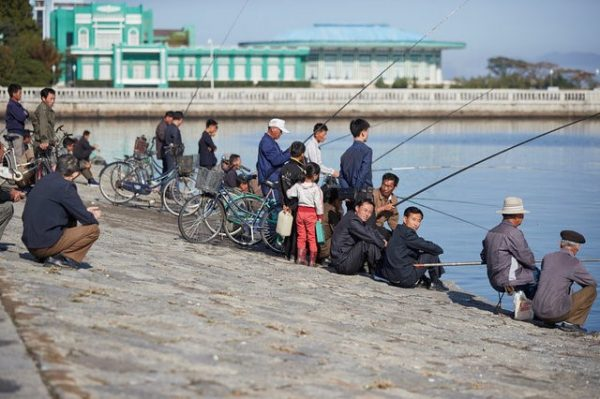 People fish in the Bay of Wonsan, North Korea October 2016. The hotel in the background is scheduled for refurbishment as part of a massive project to redesign the entire city center. (Christian Peterson-Clausen/Handout via Reuters)