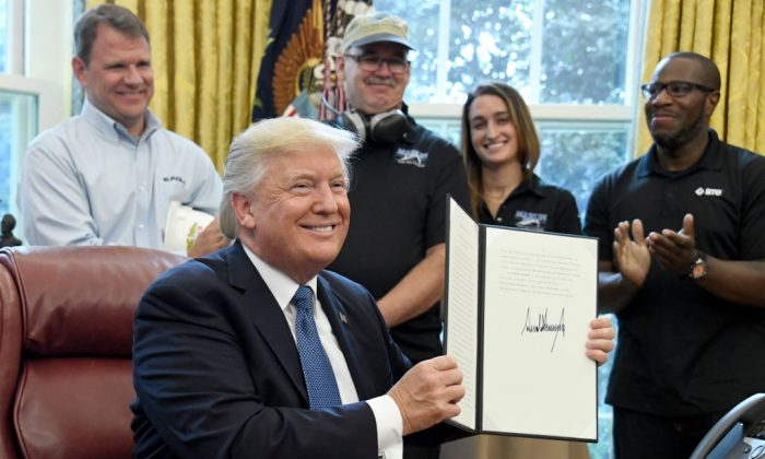 President Donald Trump displays a National Manufacturing Day Proclamation after signing it in the Oval Office of the White House in Washington, DC on Oct. 6, 2017. (Ron Sachs - Pool/Getty Images)