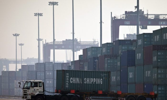 A truck transports a container to be loaded onto a ship at a port in Tianjin, China. Cheap Chinese imports have resulted in a startling loss of manufacturing jobs in Canada and the United States. (AP Photo/Alexander F. Yuan)