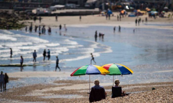 People sit beside the sea as they enjoy the fine weather on the beach in Lyme Regis in Dorset, England. (Matt Cardy/Getty Images)