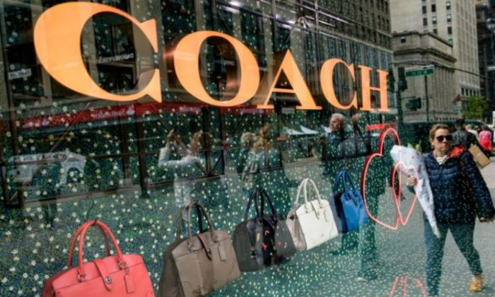 A woman walks past Coach bags in a window of Macy's flagship store, May 12, 2017 in the Herald Square neighborhood in New York City. (Drew Angerer/Getty Images)