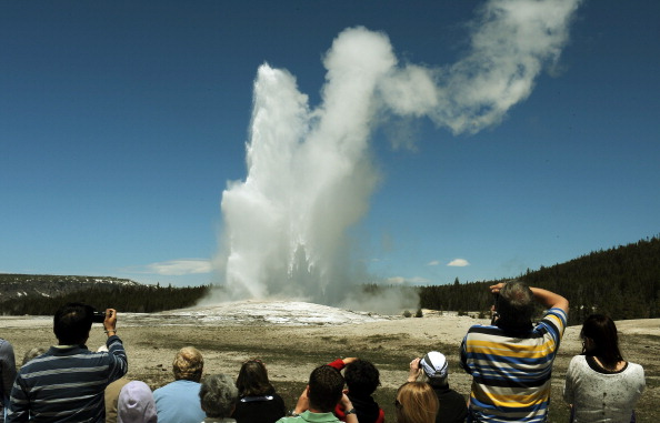 Tourists watch the 'Old Faithful' geyser which erupts on average every 90 minutes in the Yellowstone National Park, Wyo., in this file photo. (MARK RALSTON/AFP/Getty Images)