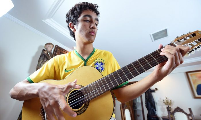 Joao de Assis, who was born with 12 fingers, plays guitar in his home in Brasilia, on June 21, 2014. (AFP PHOTO/ EVARISTA SA)