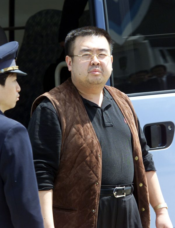Escorted by an immigration officer, a man believed to be Kim Jong-Nam, son of North Korean leader Kim Jong-Il, gets off a bus to board an ANA905 (All Nippon Airways) airplane at Narita airport near Tokyo, 04 May 2001. (Toshifumi Kitamura/AFP/Getty Images)