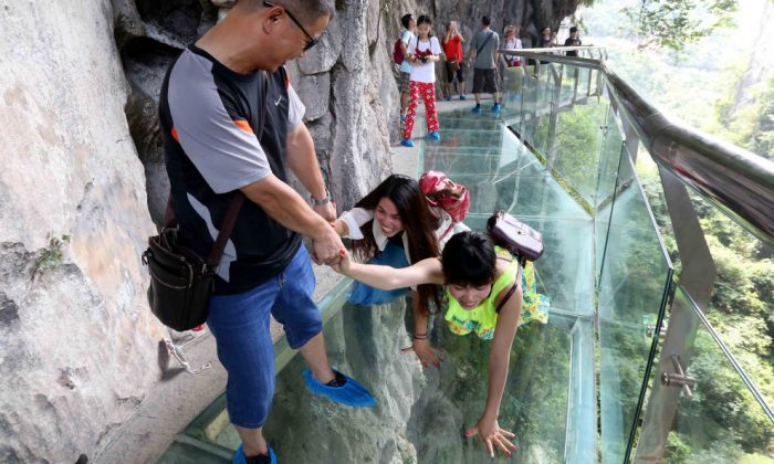 A man helping two women go across the glass-bottomed skywalk at Shimenxian Lake in Rongan in southern China's Guangxi Province.