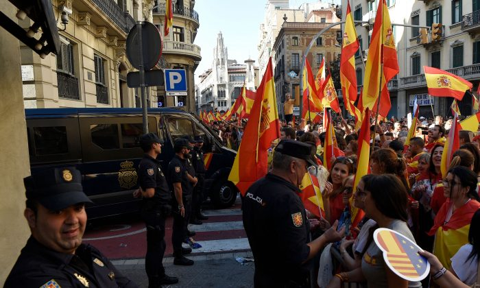 Protesters congratulate Spanish policeman after a demonstration called by Societat Civil Catalana (Catalan Civil Society) to support the unity of Spain on Oct. 8 in Barcelona. (LLUIS GENE/AFP/Getty Images)