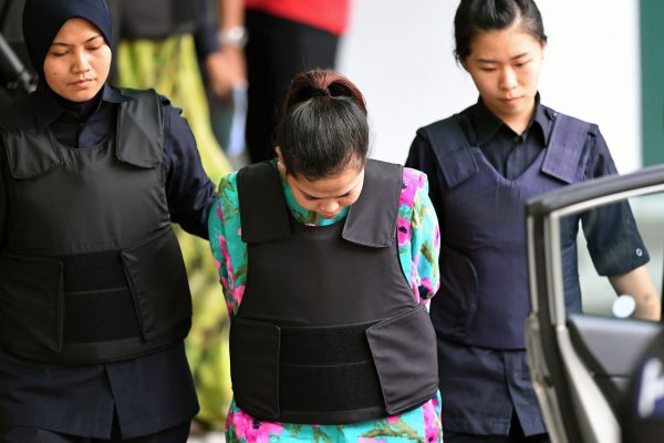 Indonesian defendant Siti Aisyah is escorted by police personnel following her appearance at the Malaysian Chemistry Department in Petaling Jaya, outside Kuala Lumpur on October 9, 2017, as part of the ongoing trial for her alleged role in the assassination of Kim Jong-Nam, the half-brother of North Korean leader Kim Jong-Un. (Mohd Rasfan/AFP/Getty Images)