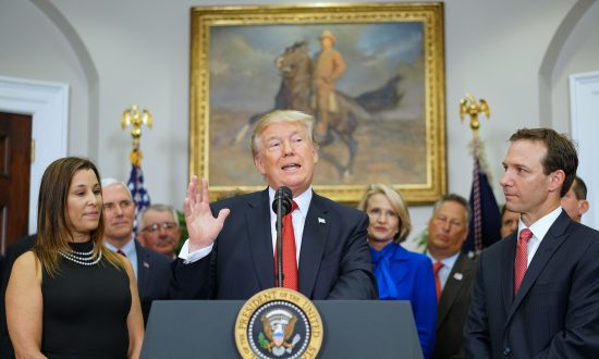 President Donald Trump, flanked by business owners Leslie Baudry (L) and Rich Baudry, speaks before signing an executive order on health insurance on Oct. 12, 2017. (MANDEL NGAN/AFP/Getty Images)