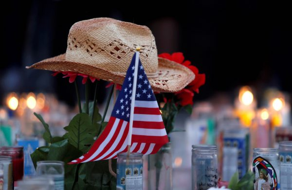 FILE PHOTO - A hat rests on flowers in a makeshift memorial during a vigil marking the one-week anniversary of the October 1 mass shooting in Las Vegas, Nevada U.S. October 8, 2017. (Reuters/Las Vegas Sun/Steve Marcus)