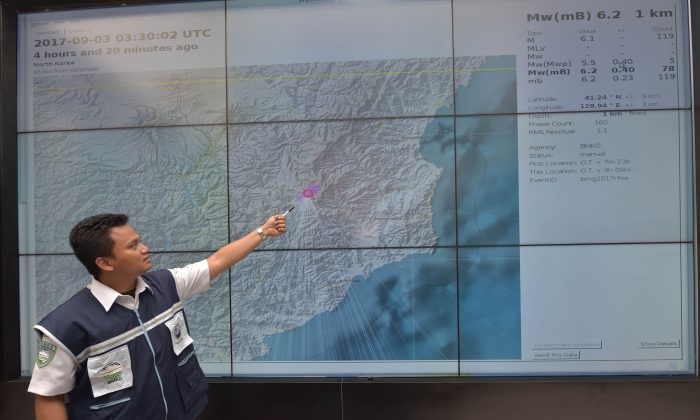 An Indonesian official at Indonesia's Meterological, Climatological and Geophysical Agency (BMKG)  points to a map of North Korea showing where the agency recorded a magnitude-6.2 earthquake caused by a North Korean nuclear test on Sept. 3, 2017. (Adek Berry/AFP/Getty Images)