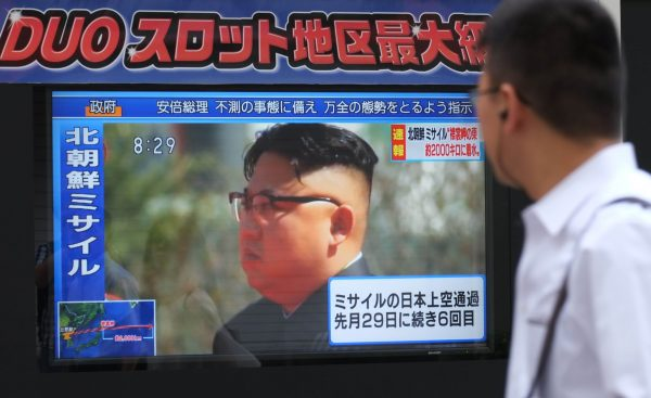 Pedestrians walk past a television screen broadcasting a news report showing North Korean leader Kim Jong-Un, in Tokyo on September 15, 2017, following a North Korean missile test that passed over Japan. (Kazuhiro Nogi/AFP/Getty Images)