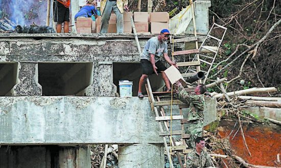 Members of the U.S. Army deliver boxes of food and water up a makeshift ladder to residents in Utuado, Puerto Rico, who were cut off after a bridge collapsed, on Oct. 5. (JOE RAEDLE/GETTY IMAGES)