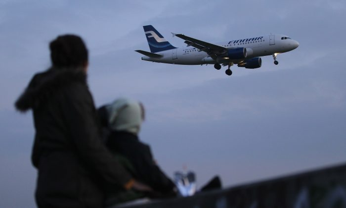 A woman and her two children watch a Finnair passenger plane arrive at Tegel Airport on Oct. 17, 2011, in Berlin. (Sean Gallup/Getty Images)