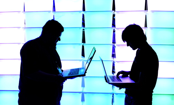 Participant hold their laptops in front of an illuminated wall at the annual Chaos Computer Club (CCC) computer hackers' congress. (Photo by Patrick Lux/Getty Images)