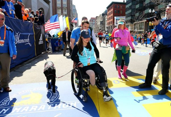 Boston Marathon bombing survivors Patrick Downes and Jessica Kensky celebrate at the finish line with their dog Rescue after Downes completed the 120th Boston Marathon on April 18, 2016 in Boston, Massachusetts. (Maddie Meyer/Getty Images)