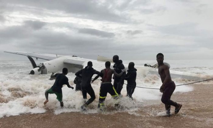 People pull the wreckage of a propeller-engine cargo plane after it crashed in the sea near the international airport in Ivory Coast's main city, Abidjan, October 14, 2017. (Reuters/Ange Aboa)