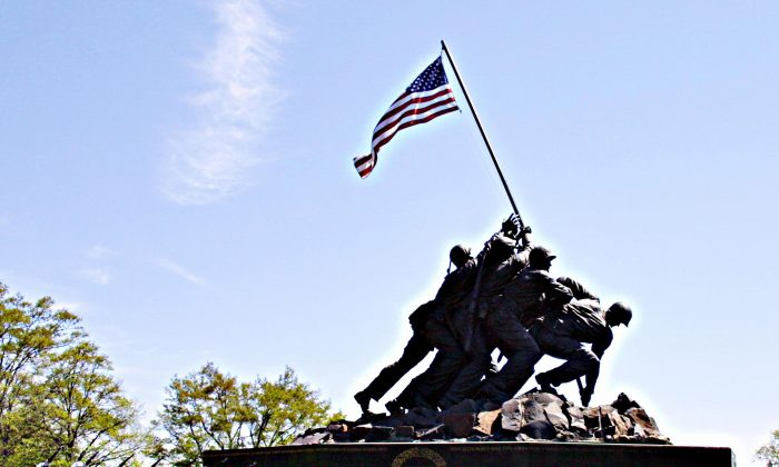 In this file photo, a U.S. Marine Corp squad practices in front of the Iwo Jima Memorial on April 26, 2005 in Arlington, VA. The memorial depicting the famous flag raising on the island of Iwo Jima during World War II honors all Marines who have fallen in all war and can be taken as a symbol of unity in the United States. (KAREN BLEIER/AFP/Getty Images)