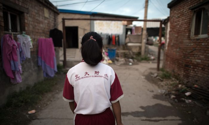 """In this picture taken on August 17, 2017, a girl walks toward a goalpost on a street in a migrant village on the outskirts of Beijing. Surrounded by the sleek hi-tech campuses and luxury condominiums of """"Beijing's Silicon Valley"""", migrants from the countryside recreate village life, cooking in outdoor communal areas, playing cards and showering in the street. But their community's days are numbered. (NICOLAS ASFOURI/AFP/Getty Images)"""