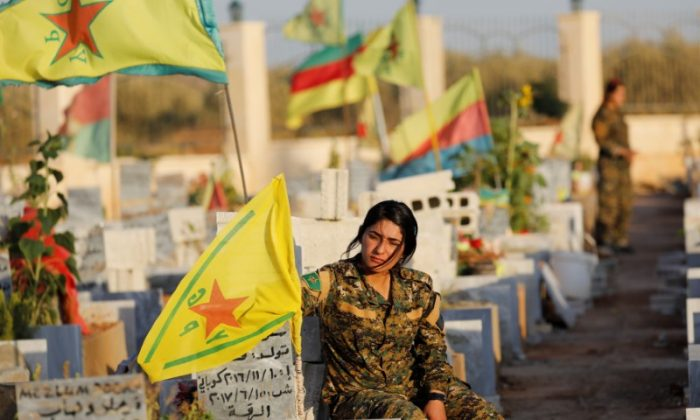 Fighters of Syrian Democratic Forces visit the graves of their late comrades at a cemetery for those fighters killed during fightings with ISIS terrorists in Kobani, Syria October 11, 2017. Picture taken October 11, 2017.    (Reuters/Erik De Castro)