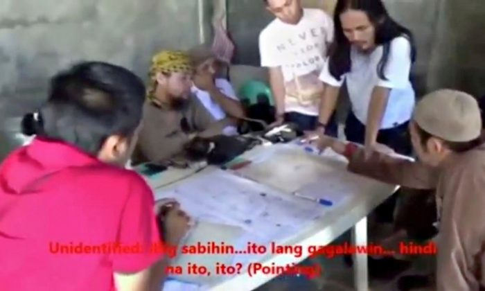 Men identified by Philippines Intelligence officers as Isnilon Hapilon (2nd L, yellow headscarf) and Abdullah Maute (2nd R, standing, long hair) are seen in this still image taken from video released by the Armed Forces of the Philippines on June 7. (Armed Forces of the Philippines/Handout via REUTERS TV)