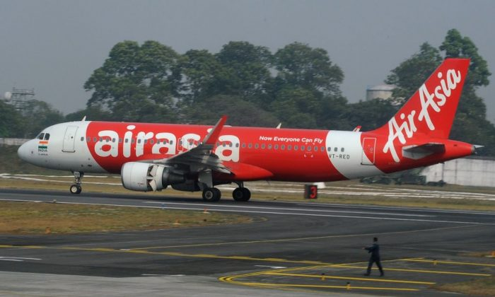 An Indian airport staff member walks next to an AirAsia airplane after it landed on its inaugural flight from New Delhi to Bagdogra Airport, some 12 miles from Siliguri, on Feb. 19, 2017. (Diptendu Dutta/AFP/Getty Images)