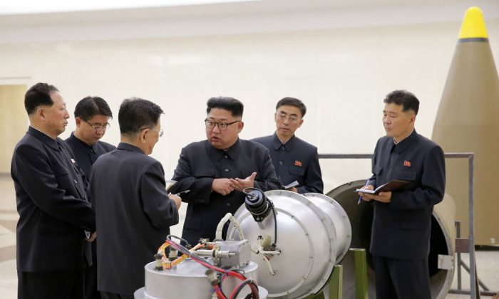 In this undated photo released by North Korea's official Korean Central News Agency (KCNA) on Sept. 3, 2017, North Korean leader Kim Jong Un (C) looking at a metal casing with two bulges at an undisclosed location. (STR/AFP/Getty Images)