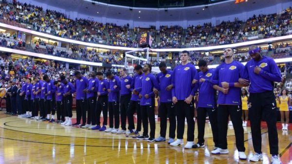 The Los Angeles Lakers players lock arms during the national anthem before the start of the game against the Minnesota Timberwolves on September 30, 2017 at the Honda Center in Anaheim, California. (Robert Laberge/Getty Images)