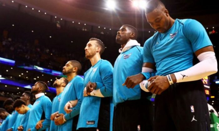 Dwight Howard #12 of the Charlotte Hornets, right, links arms with teammates during the national anthem before the game against the Boston Celtics at TD Garden on October 2, 2017 in Boston, Massachusetts. (Photo by Maddie Meyer/Getty Images)
