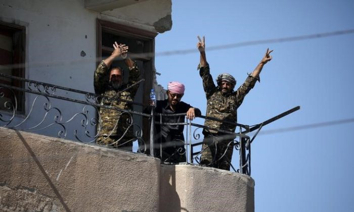 """Fighters from the Syrian Democratic Forces give the """"V"""" sign at the frontline in Raqqa, Syria on Oct. 16, 2017.      (REUTERS/Rodi Said)"""
