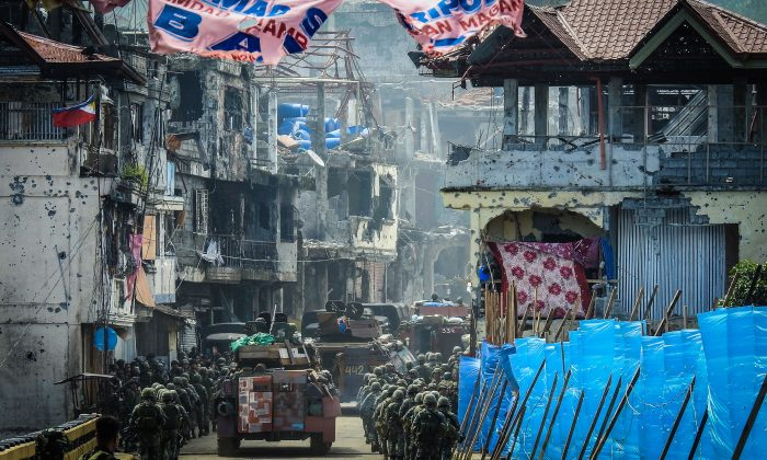 Philippine Marines, marching in formation alongside armoured personnel carriers, head to the frontline past damaged buildings in the Mapandi area of Marawi on the southern island of Mindanao on Aug. 30 as fighting between government troops and pro-ISIS state terrorists entered its 100th day.  The terrorists, who fly the black flag of the ISIS, have occupied parts of Marawi for almost five months, defying airstrikes and  artillery barrages, with parts of the city of 200,000 people left in ruins, leaving 45 civilians, 617 militants, and 133 soldiers killed in the ongoing conflict. (FERDINANDH CABRERA/AFP/Getty Images)