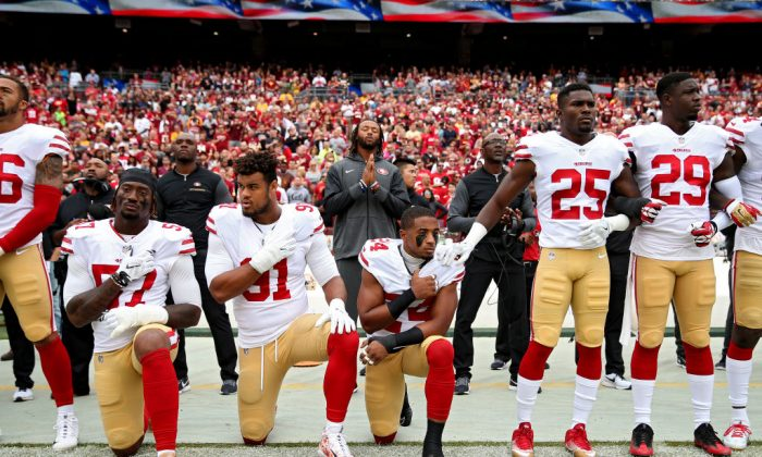 K'Waun Williams #24, Arik Armstead #91, and Eli Harold #57 of the San Francisco 49ers kneel while holding their hands over their chest during the U.S. national anthem before playing against the Washington Redskins at FedExField in Landover, Md., on Oct. 15, 2017. (Patrick Smith/Getty Images)