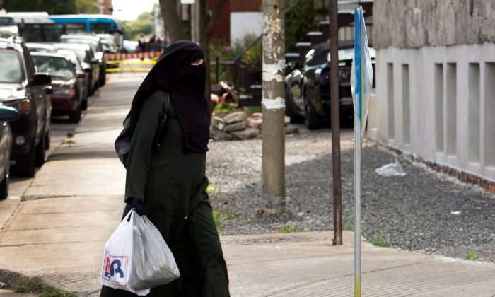 File photo of a woman wearing a niqab as she walks in a street in Montreal. Quebec lawmakers have passed a religious neutrality bill that obliges citizens to uncover their faces while giving and receiving state services. (The Canadian Press/Ryan Remiorz)