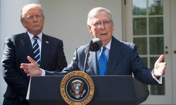 US President Donald Trump listens to Senate Majority Leader Mitch McConnell (R–Ky.), speak to the media in the Rose Garden of the White House in Washington on Oct. 16, 2017. (SAUL LOEB/AFP/Getty Images)