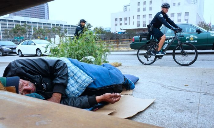 Los Angeles Police Department officers patrol on bicycles past a homeless man on a downtown sidewalk in Los Angeles, California on June 7, 2017. (FREDERIC J. BROWN/AFP/Getty Images)