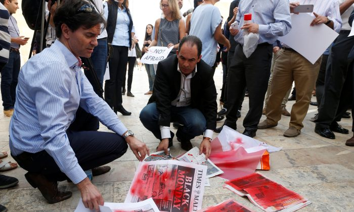 Journalists Herman Grech (L) and Dione Borg place printouts of newspaper pages, sprayed with red paint and reporting the assassination of investigative journalist Daphne Caruana Galizia in a car bomb attack on Oct 16., during a protest against her murder, in Valletta, Malta.  REUTERS/Darrin Zammit Lupi