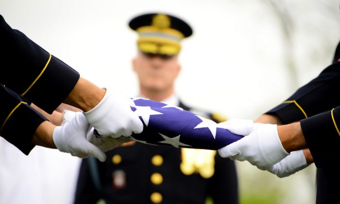 Soldiers of Delta Company, 3d U.S. Infantry Regiment (The Old Guard), finish folding a flag during the interment of Lt. Col. Don C. Faith Jr., commander, 1st Battalion, 32nd Infantry Regiment in Arlington National Cemetery, Va., in this file photo. (U.S. Army Photo by Sgt. Jose A. Torres Jr.)