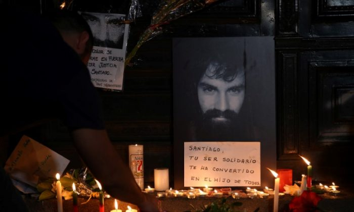 A man lights candles next to a portrait of Santiago Maldonado, a protester who went missing since security forces clashed with indigenous activists in Patagonia on August 1, 2017, placed at the entrance of a  judicial morgue in Buenos Aires, Argentina October 20, 2017.  (Reuters/Marcos Brindicci)