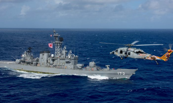 A U.S. MH-60S Sea Hawk flies by Japan's Maritime Self-Defense Force ship JS Shimakaze above waters around Okinawa southwest of the Korean peninsula, Oct. 9, 2017. Japan, the United States, and South Korea launched a joint ballistic missile tracking drill on Oct. 24, 2017. (U.S. Navy via REUTERS)