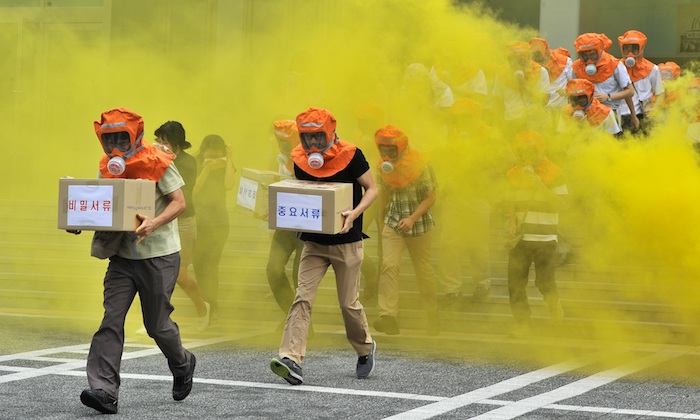 South Koreans run out of a building during a civil defence drill in Seoul on August 22, 2012. Researchers at Harvard's Belfer Center for Science and International Affairs have published a report about North Korea's biological weapons program that calls for better preparations. (JUNG YEON-JE/AFP/GettyImages)