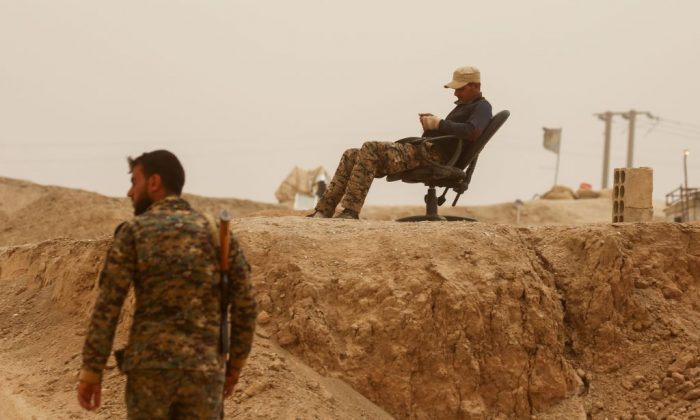 A member of the Kurdish People's Protection Units (YPG) rests on a chair as another walks by in the town of al-Karamah, 26 kms from the ISIS group bastion of Raqa, on May 10, 2017. (Delil Souleiman/AFP/Getty Images)