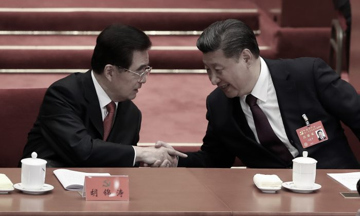 Chinese leader Xi Jinping (R) shakes hands with Hu Jintao, his predecessor, during the opening session of the 19th National Congress in Beijing on Oct. 18, 2017. (Lintao Zhang/Getty Images)