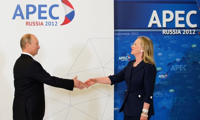 Then Secretary of State Hillary Clinton reaches out to shake hands with Russian President Vladimir Putin during the arrival ceremony for the Asian-Pacific Economic Cooperation (APEC) Summit in Vladivostok on Sept. 8, 2012. (JIM WATSON/AFP/GettyImages)