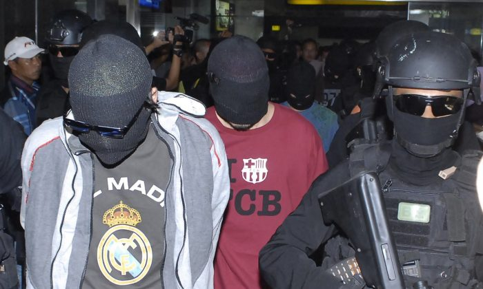 Elite Indonesian anti-terror police from Densus 88 escort four Turks arrested on arrival at Jakarta airport on Sept. 14, 2014. The four Turkish nationals were arrested in Sulawesi island and are suspected to be linked to the jihadist Islamic State group, police spokesman said. (BIMA SAKTI/AFP/Getty Images)