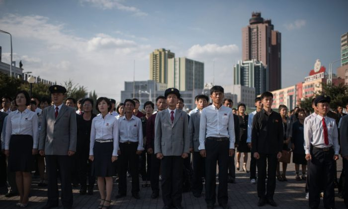 Spectators listen to a television news brodcast of a statement by North Korean leader Kim Jong-Un, before a public television screen outside the central railway station in Pyongyang on September 22, 2017.(ED JONES/AFP/Getty Images)
