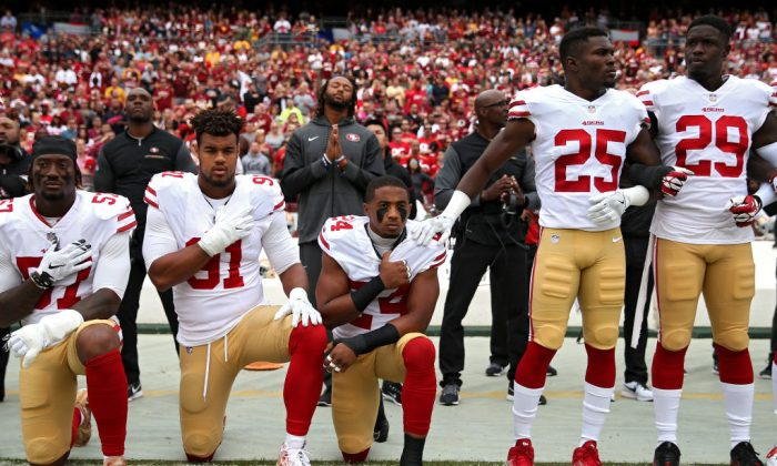 K'Waun Williams #24, Arik Armstead #91, and Eli Harold #57 of the San Francisco 49ers kneel while holding their hands over their chest during the national anthem before playing against the Washington Redskins at FedExField in Landover, Maryland on Oct. 15, 2017. (Photo by Patrick Smith/Getty Images)