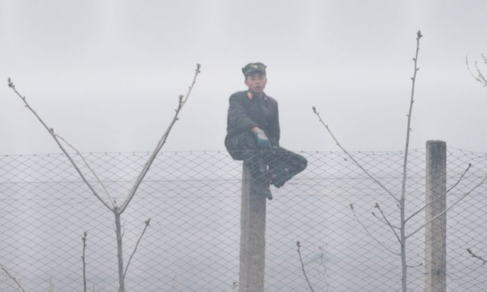 A North Korean soldier sits on a fence post near Sinuiju, opposite the Chinese border city of Dandong on April 15, 2017. (Johannes Eisele/AFP/Getty Images)