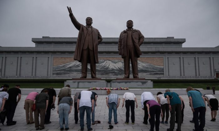 A group of tourists—on command from their guide to bow deeply—bow before statues of late North Korean leaders Kim Il-Sung (L) and Kim Jong-Il (R), on Mansu Hill in Pyongyang on July 23, 2017. North Korean authorities have increased the amount of 24-hour guarding at sites like this to prevent vandalism. (ED JONES/AFP/Getty Images)