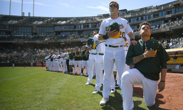 Bruce Maxwell No. 13 of the Oakland Athletics kneels in protest next to teammate Mark Canha No. 20 duing the singing of the national anthem prior to the start of the game against the Texas Rangers at Oakland Alameda Coliseum on Sept. 24, 2017, in Oakland, Calif.  (Thearon W. Henderson/Getty Images)