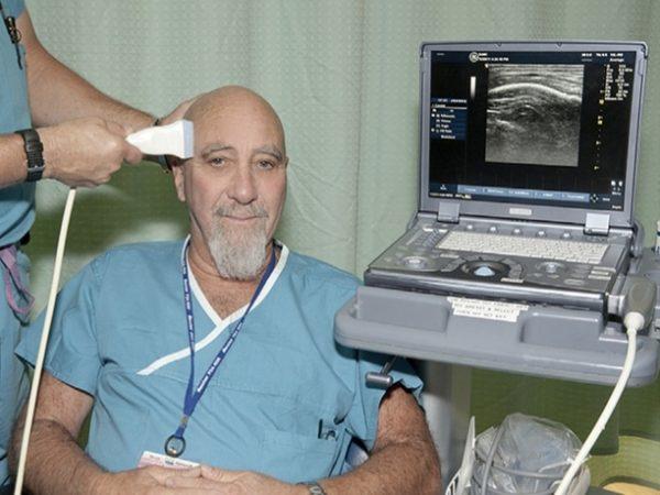 Dr. Stuart Hameroff demonstrates transcranial ultrasound treatment for improving mood. (Courtesy of Dr. Stuart Hameroff)